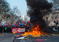 Protestierende mit Fähnchen und einem Plakat hinter brennenden Barrieren. (Bild: Keystone)