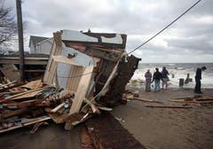Menschen begutachten die Schäden nach dem Sturm. (Bild: Keystone)