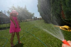 Das Mädchen geniesst eine Abkühlung aus dem Gartenschlauch. (Bild: Keystone)