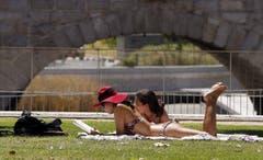 Zwei Touristinnen beim Sonnenbaden in einem Park in Spaniens Hauptstadt Madrid. (Bild: MARISCAL (EPA EFE))