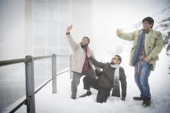 Posieren im Schnee, und das mitten im Sommer: Touristen beim Selfie auf dem verschneiten Säntisgipfel (14.7.2016). (Bild: Ralph Ribi)