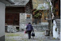 Eine Dorfbewohnerin auf dem Weg in ihr Zuhause. (Bild: KEYSTONE/Gian Ehrenzeller)