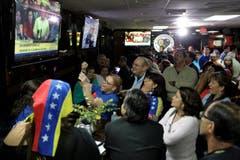 Menschen versammeln sich vor dem Fernseher in einem Restaurant in Doral (Florida). (Bild: Keystone)