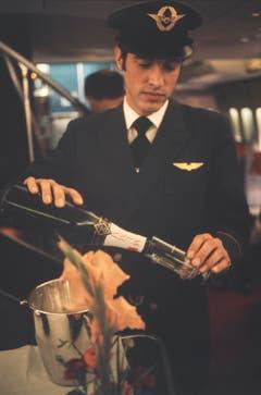 Champagner gefällig? Ein Steward in der First Class einer frühen 747 der Swissair. Im Hintergrund ist die Wendeltreppe sichtbar, die zur Lounge auf dem Oberdeck führte. (Bild: ETH-Bibliothek/Bildarchiv/Stiftung Luftbild Schweiz/Swissair)