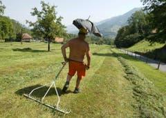 Bauer Hansruedi Sigrist aus Giswil im Kanton Obwalden hat sich für die Arbeit aus einem Helm und einem abgesägten Regenschirm einen Sonnenschutz gebastelt. (Bild: Keystone)