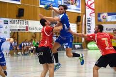 Steigt höher als alle anderen: Tobias Baumgartner vom HC Kriens-Luzern gegen die Winterthurer Spieler Mila Corocic (links) und Marcel Hess. (Bild: Nadia Schärli / Neue LZ)