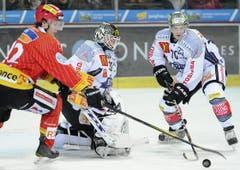 Gaetan Haas vom EHC Biel kämpft mit Zugs Goalie Jussi Markkanen und Yannick Blaser um die Scheibe. (Bild: Keystone)