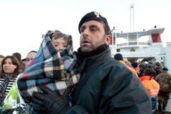 Ein Polizeibeamter mit einem Kleinkind vor der Fähre in Porto Santo Stefano. (Bild: Keystone / AP)
