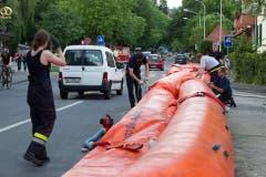 Mitarbeiter der Feuerwehr installieren im Marzili-Quartier Schutzschläuche gegen Hochwasser. (Bild: Keystone / Peter Klaunzer)