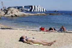 Eine Touristin sonnt sich vor Giglio (Bild: Keystone / EPA)