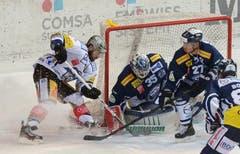 Der Zuger Henrik Zetterberg (links) versucht Ambris Goalie Cory Schneider (Mitte) und Verteidiger Richard Park, (Zweiter rechts) zu bezwingen. (Bild: Keystone)