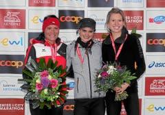 Blumen für die schnellsten Damen: Die Siegerin Franziska Inauen (M, Schweiz), die Zweitplatzierte Nicole Lohri (L, Schweizd) und die Drittplatzierte Isabell Gindrat-Keller (R, Schweiz) freuen sich über ihren Erfolg. (Bild: swiss-image.ch/Photo Andy Mettler)