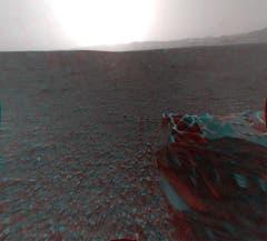 Auch hinter dem Rover ist die Landschaft karg. In der Distanz lässt sich auch hier wieder der Rand des«Gale»-Kraters erkennen. Im Vordergrund ist eines der sechs Räder von«Curiosity» zu sehen. Die 3D-Stereo-Aufnahme ist wegen des Sonnenscheins leichtüberbelichtet. (Bild: Nasa / JPL-Caltech)
