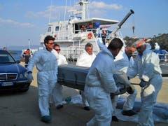 Bergungsleute bringen einen Toten aufs Festland. (Bild: Keystone / EPA)