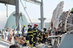 Feuerwehrleute suchen in einer zerstörten Fabrik in Mirandola nach Opfern. (Bild: Keystone / AP)