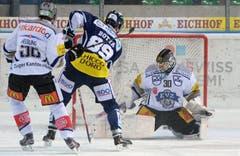 Der Zuger Timo Helbling (links) versucht Ambris Roman Botta (Mitte) erfolglos am Fuehrungstreffer zum 1:0 gegen Goalie Jussi Markkanen (rechts) zu hindern. (Bild: Keystone)
