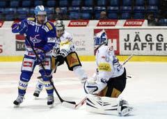 Kloten Flyers Stuermer Cyrill Buehler, von links, gegen EV Zug Stuermer Fabian Sutter und Torhueter Eero Kilpelainen. (Bild: Keystone)