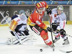 Gaetan Haas vom EHC Biel zirkelt die Scheibe um Zugs Goalie Jussi Markkanen und Yannick Blaser. (Bild: Keystone)