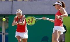 Timea Bacsinszky (links) und Martina Hingis gehen beide auf den Ball los. (Bild: AP Photo/Charles Krupa)