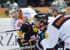 Berner Thomas Ruefenacht (mitte) und der Zuger Robin Grossmann (links) kämpfen um den Puck. (Bild: Keystone/Lukas Lehmann)