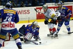 Kloten Flyers -Goalie Ronnie Rüegerversucht die Scheibe vor dem Zuger Stürmer Reto Suri zu sichern.