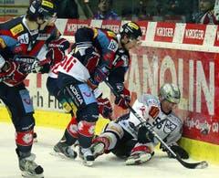 Zugs Verteidiger Timo Helbling, am Boden, gegen Kloten Flyers Stürmer Simon Bodenmann, Mitte, und Stürmer Arnaud Jacquemet.