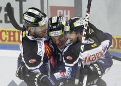 Andy Wozniewski, Damien Brunner (Torschütze) und Fabian Schnyder (von links) feiern das 4:3 in der Overtime. (Bild: Keystone/Urs Flüeler)