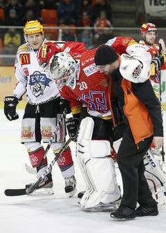 Biels Goalie Reto Berra wird verletzt vom Eis begleitet.