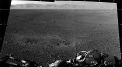 Das sind die ersten zwei hochaufgelösten Bilder der Marsoberfläche, die von den Navigationskameras auf dem Mast des Mars-Rovers«Curiosity» auf die Erde gelangten. Am Horizont lässt sich der Rand des Kraters«Gale» erkennen, in dem der Rover gelandet war. Die beiden Einbuchtungen unmittelbar vor dem Rover rühren von den Raketendüsen des Landekrans. (Bild: Nasa / JPL-Caltech)