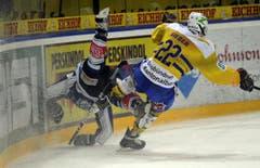Ein Zuger Spieler wird weggeräumt von Lukas Sieber vom HC Davos. (Bild: Keystone)