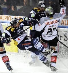 Pascal Müller fliegt neben EVZ-Stürmer Josh Holden aufs Eis. (Bild: Keystone)