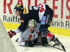 Kloten Flyers Stürmer Samuel Walser, oben, gegen EV Zug Stuermer Björn Christen.
