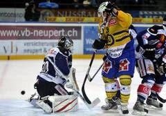 Der Davoser Gregory Sciarone (mitte) scheitert an EVZ Goalie Jussi Markkanen (links). (Bild: Keystone/Sigi Tischler)