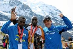 Sieger Gikuni Geoffrey Ndungu (Mitte), der Zweitplatzierte Petro Mamo und Viktor Roethlin als Dritter posieren für das Siegerfoto (Bild: Swiss Image / Remy Steinegger)