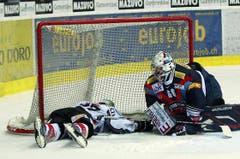 Kloten Flyers Torhüter Ronnie Rüeger, links, wird von Zugs Verteidiger Andy Wozniewski umgefahren.