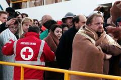 Mitarbeiter des Italienischen Roten Kreuzes versorgen die gestrandeten Passagiere mit Wolldecken. (Bild: Keystone / AP)