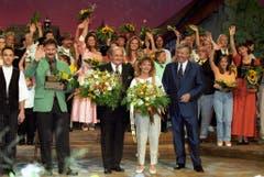 """Karl Moik (rechts) am Ende der Sendung """"Grand Prix der Volksmusik 1997 im Hallenstadion Zürich. In der Mitte, neben Sepp Trütsch, steht Sandra Weiss, die den Grand Prix gewonnen hatte. (Bild: Keystone)"""