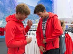 Ruderer Barnabe Delarze (links) schaut sich die Kleidung mit einem Teamkollegen an. (Bild: Keystone / Georgios Kefalas)