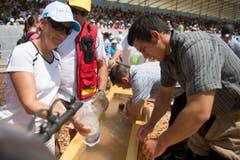 Festbesucher bestürmen den Schwingerbrunnen für eine Abkühlung. (Bild: Keystone/Urs Flüeler)
