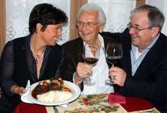Monika Fasnacht serviert Walter Roderer ein Ochsenschwanz-Ragout, Vic Eugster (rechts) prostet zu. (Bild: Archiv Neue LZ)