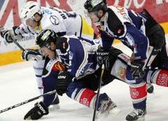 Die Zuger Timo Helbling, links, und Patrick Fischer, rechts, im Kampf gegen Mattia Bianchu von Ambri.