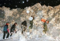 Es ist der 22. Februar 1999. Rettungskräfte versuchen um 2 Uhr morgens die Schneewand in Evolène zu durchbrechen. Eine Lawine hat den Skiort am Tag zuvor erschüttert und zahlreiche Chalets zerstört. Zu diesem Zeitpunkt sind zwei Menschen verstorben, zehn werden noch vermisst. (Bild: Keystone/Fabrice Coffrini)