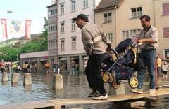 Zahlreiche Schaulustige sind nach Rorschach gekommen, um das Hochwasser zu sehen. Die Strasse können sie nur über einer Holzbrücke überqueren. (Bild: Keystone)
