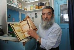 Jüdisches Pilgerfest zur Ghriba-Synagoge auf der Insel Djerba - Tunesiens Oberrabbiner Haim Bittan in seinem kleinen Laden mit einem Buch über die Geschichte des tunsischen Rabbinats.(Fotografin: Katharina Eglau)
