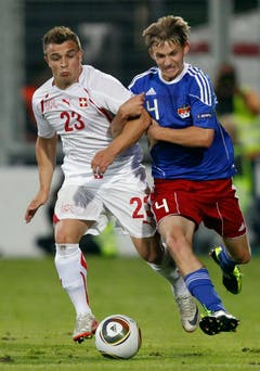 Switzerland's Xherdan Shaqiri, left, fights for the ball with Liechtenstein's Martin Rechsteiner, right, during a friendly soccer match between Liechtenstein and Switzerland at the Rheinpark Stadium in Vaduz, Liechtenstein, Wednesday, August 10, 2011. (KEYSTONE/Peter Klaunzer)