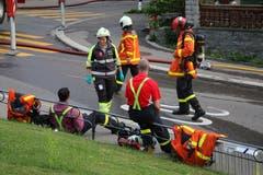 Die Brandbekämpfung unter Atemschutz wie am Donnerstagabend im Linsebühl ist härtester Körpereinsatz. Was man den Feuerwehrleuten nach dem Einsatz auch ansieht: Kurze Pause auf der Singenbergstrasse. (Bild: Reto Voneschen)