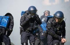 Bei der Übung der Polizeikorps von Luzern, Nid- und Obwalden in Schüpfheim schützen sich Polizisten vor Tränengas (Bild Corinne Glanzmann, 25. Mai 2018).