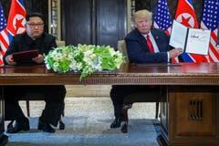 US-Präsident Donald Trump hält den unterzeichneten Vertrag in die Kamera. (Bild: AP Photo/Evan Vucci)