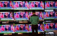 Das Treffen der beiden Machthaber Trump und Kim wurde im TV übertragen. Ein Mann steht in Hong Kong vor einem Schaufenster mit unzähligen TV-Monitoren und verfolgt eine Newssendung, welche das Treffen gerade überträgt. (Bild: AP Photo/Vincent Yu)