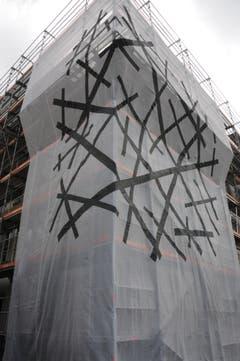 Das mit Ornamenten gestaltete Gerüstschutznetz von Roland Heini an der Westecke des Gebäudes stellt eine informelle Form dar. Die Bewegungen sind chaotisch, Überschneidungen oder Treffen sind zufällig.